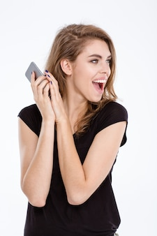 Portrait of a young woman screaming on somebody while closed microphone on phone with palm isolated on a white background