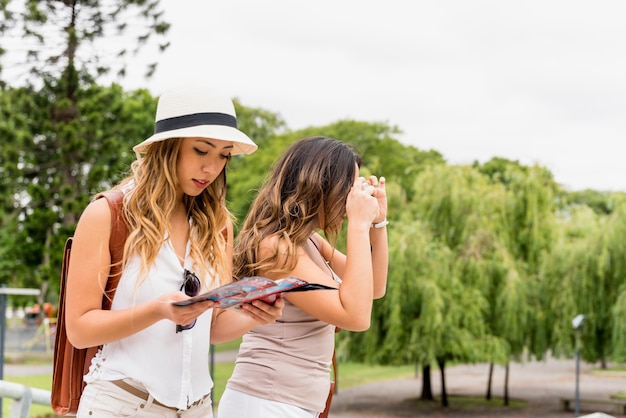 Portrait of a young woman searching in the map while her female tourist taking photograph from camera