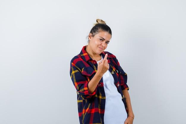 Ritratto di giovane donna che mostra venire qui gesto con la mano, in piedi lateralmente in camicia a scacchi e sembra attraente.