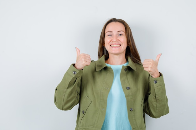 Portrait of young woman showing double thumbs up in t-shirt, jacket and looking jolly front view
