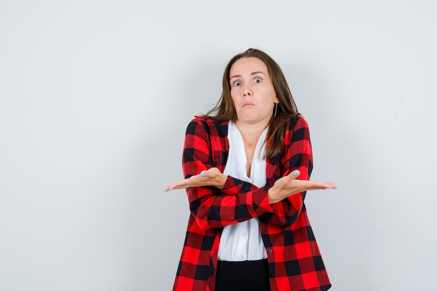Ritratto di giovane donna che mostra un gesto impotente in abiti casual e sembra una vista frontale senza tracce