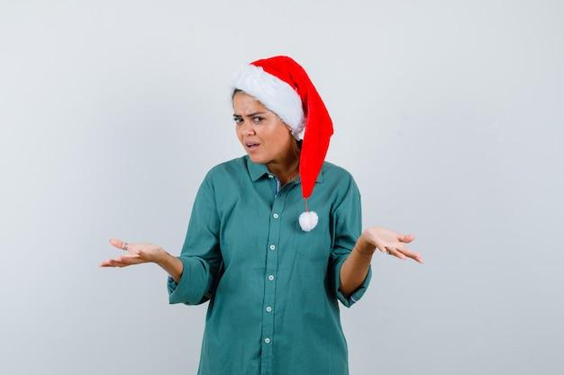 Ritratto di giovane donna che mostra un gesto impotente in camicia, cappello da babbo natale e sembra una vista frontale esitante