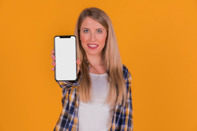 Portrait of a young woman showing her mobile phone against orange background