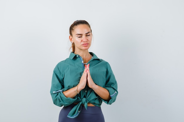 Portrait of young woman showing namaste gesture in green shirt and looking hopeful front view