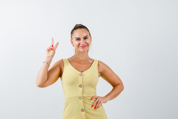 Portrait of young woman showing peace gesture in yellow dress and looking merry front view