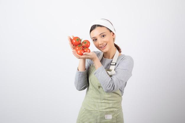 Ritratto di giovane donna che mostra pomodori rossi su muro bianco