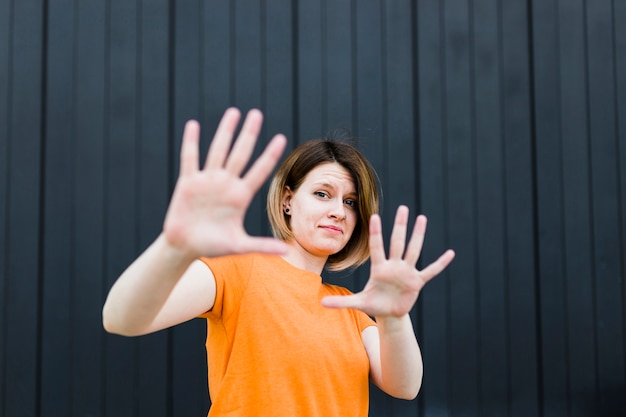 Portrait of a young woman showing stop gesture against black wall
