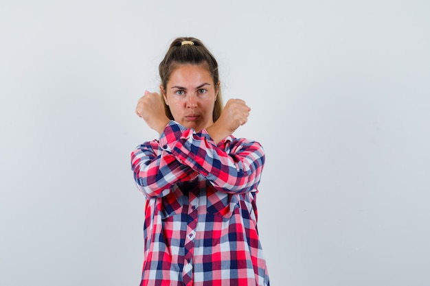 Ritratto di giovane donna che mostra il gesto di arresto con i pugni incrociati in camicia casual e guardando grave vista frontale