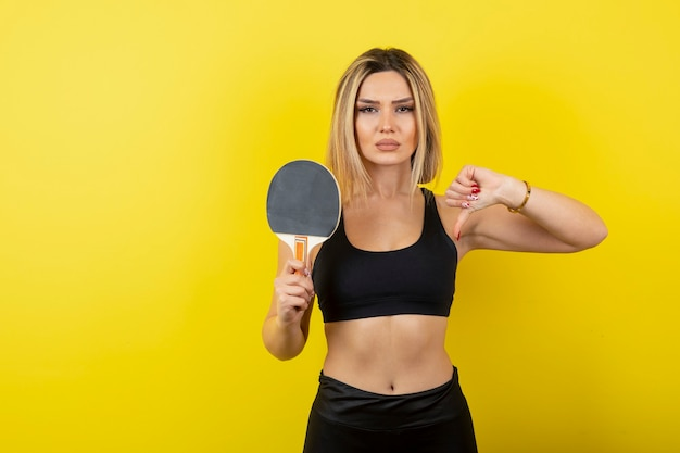 Portrait of young woman showing thumb down and holding table tennis racket.