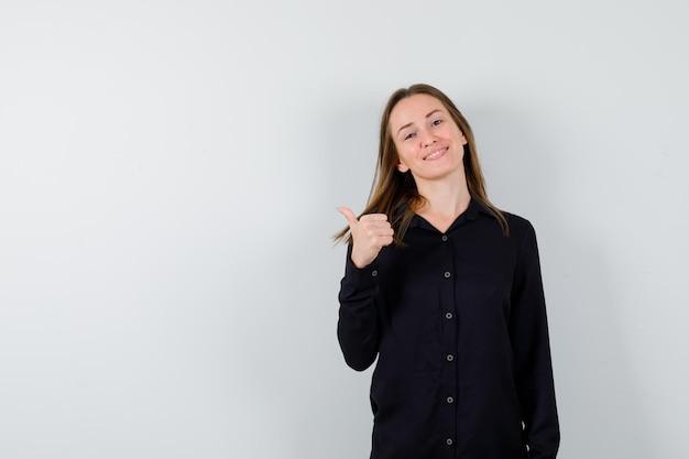 Ritratto di giovane donna che mostra i pollici in su