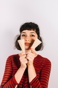 Portrait of a young woman showing two empty ice cream cone on white background