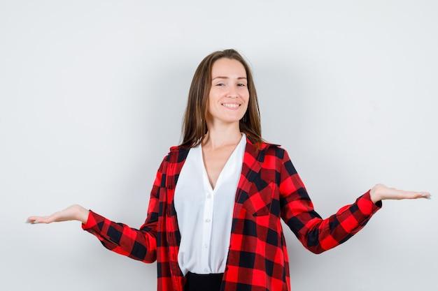 Ritratto di giovane donna che mostra gesto di benvenuto in abiti casual e sembra una vista frontale allegra