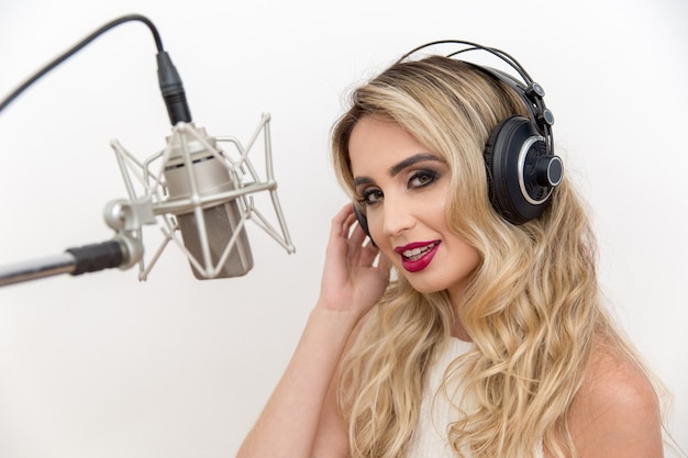 Portrait of a young woman singer with headphones in front of the microphone.