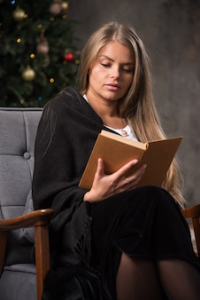 Portrait of a young woman sitting in black blanket and reading a book