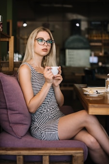 Portrait of young woman sitting in the cafe holding coffee cup looking away