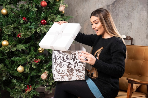 Portrait of young woman sitting and looking in a christmas present. high quality photo