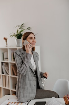 Portrait of young woman sitting on office desktop. girl in stylish suit talking on phone.