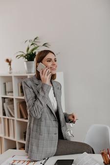 Ritratto di giovane donna seduta sul desktop dell'ufficio. ragazza in vestito alla moda che comunica sul telefono.