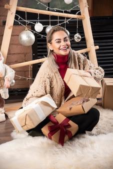 Ritratto di giovane donna seduta e in posa con regali. foto di alta qualità