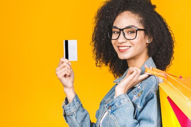 笑顔とカラフルなショッピングバッグと黄色の背景に分離されたクレジットカードとうれしそうな若い女性の肖像画。