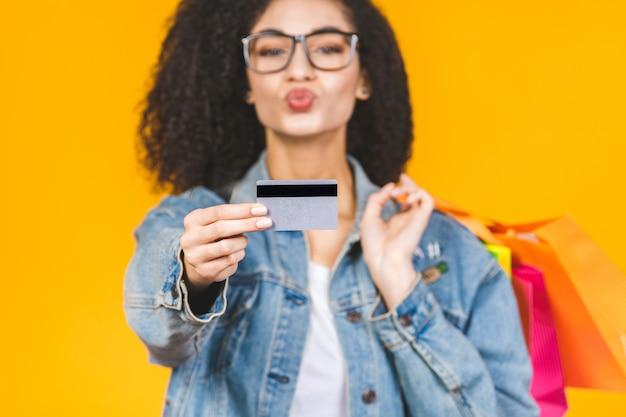 Портрет молодой женщины, улыбаясь и радостное с красочными сумок и кредитной карты, изолированных на желтом фоне.