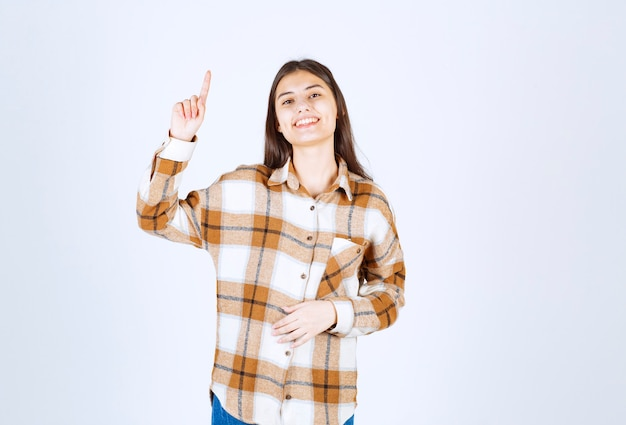 Ritratto di giovane donna che sorride felicemente sul muro bianco.