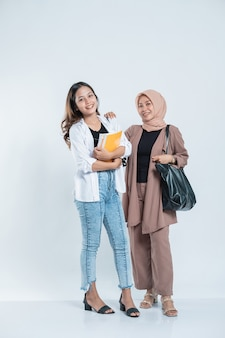 Portrait of a young woman smiling meeting a study friend carrying a bag and book on an isolated white