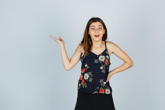 Ritratto di giovane donna che allarga il palmo della mano in camicetta, gonna e guarda la vista frontale meravigliata