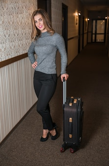 Portrait of a young woman standing in the hotel corridor with suitcase