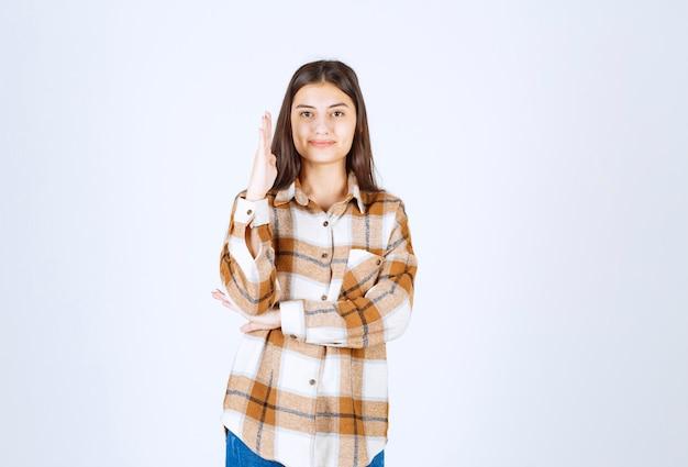 Ritratto di giovane donna in piedi e pronta a rispondere sul muro bianco.