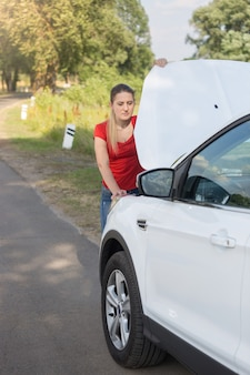 Portrait of young woman standing at the roadside and looking under the hood of broken car