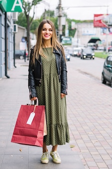 Portrait of a young woman standing on sidewalk holding shopping bags in hand