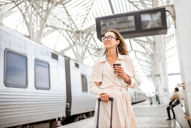Portrait of a young woman standing with coffee cup at the railway station with information board on the background