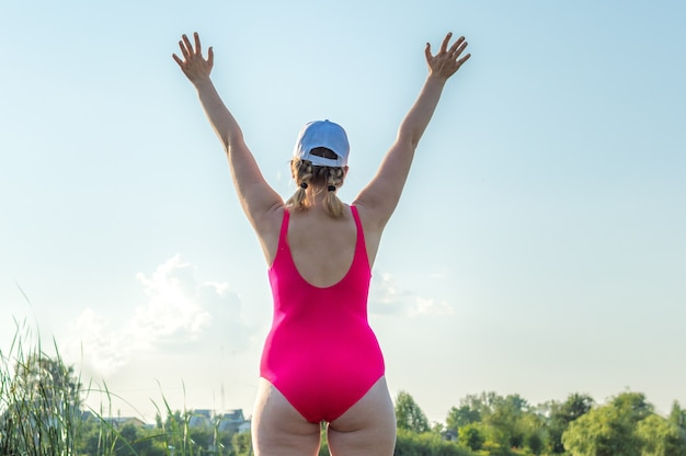 Portrait of a young woman standing with her back up with arms raised. concept body positive