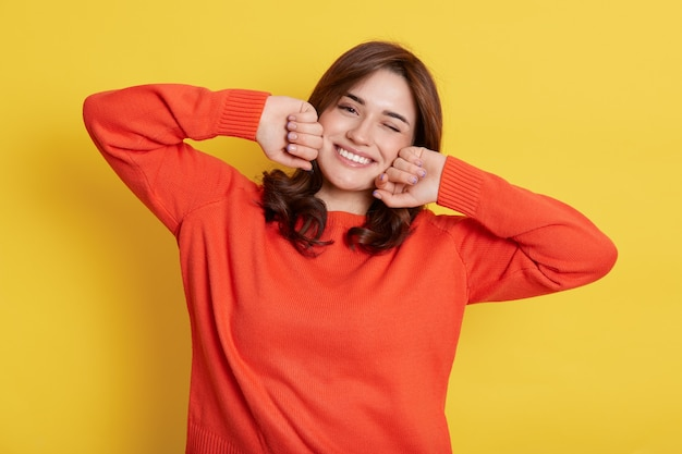 Portrait of young woman stretching after sleeping, just wakes up with excellent mood, with toothy smile, wearing orange casual sweater, keeps fists on cheeks.