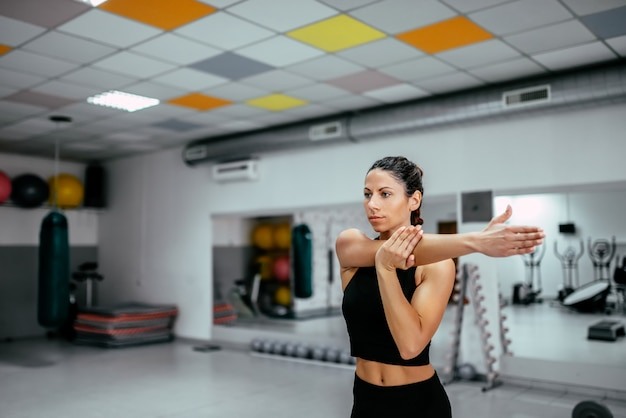 Portrait of a young woman stretching in the gym.