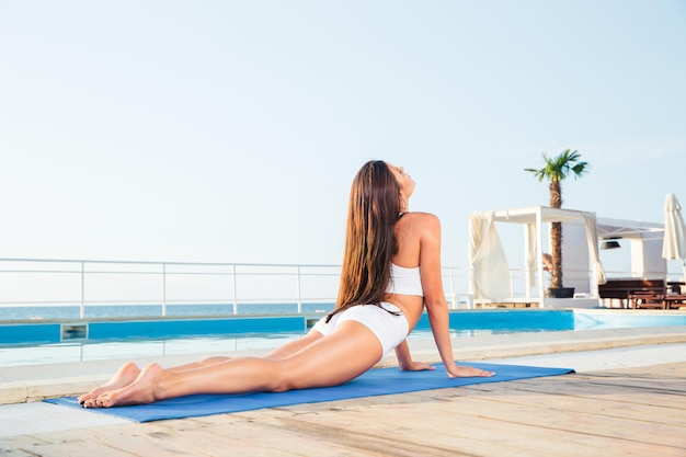 Portrait of a young woman stretching on yoga mat outdoors