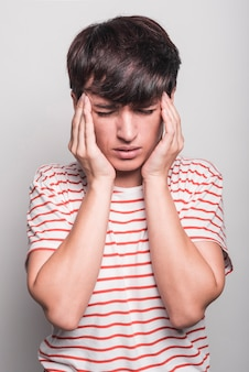 Portrait of young woman suffering from headache against white background