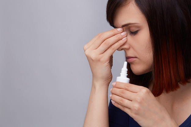 Portrait of young woman suffering from runny nose and allergy, holding fingers to nose and preparing to use nasal spray.