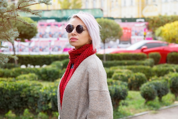 Portrait of a young woman in sunglasses on a city
