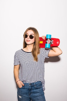 Portrait of a young woman in sunglasses posing with skateboard while standing over white wall