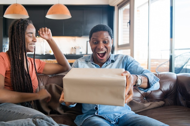 Portrait of young woman surprising her boyfriend with a gift box.