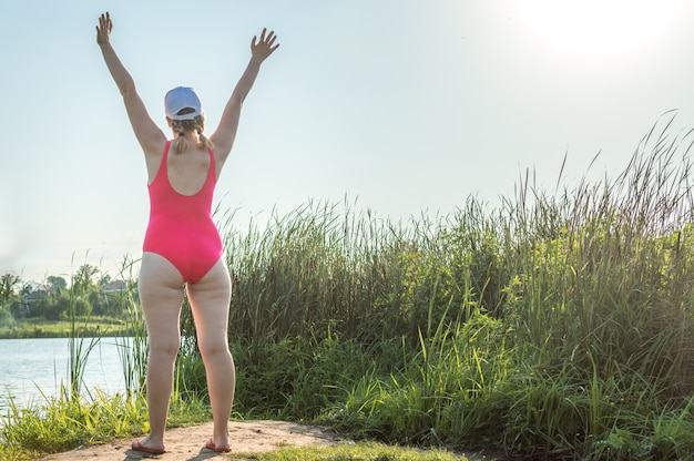 Portrait of a young woman in a swimsuit on the beach standing from the back with her hands up over her head. concept body positive