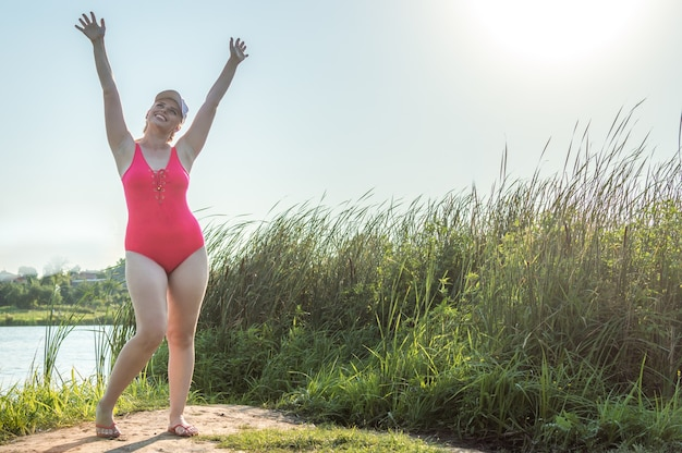 Portrait of a young woman in a swimsuit on the beach with her hands raised up over her head. concept body positive