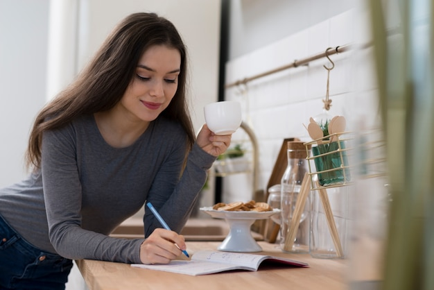 Portrait of young woman taking notes while having coffee