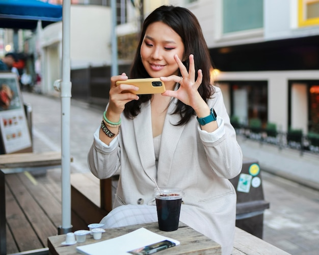 Portrait of young woman taking a photo of snack