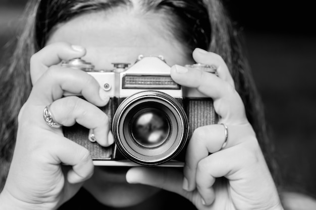 Portrait of young woman taking photos with vintage retro camera.