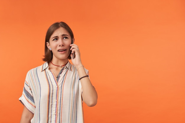 Portrait of a young woman talk on a phone. making face, not happy to hear. wearing striped shirt, teeth braces and bracelets. watching to the left at copy space against orange wall