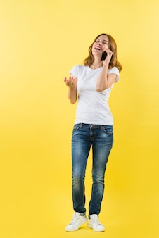 Portrait of a young woman talking on mobile phone against yellow backdrop