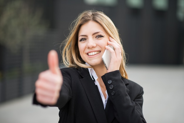 Portrait of a young woman talking on the phone and showing thumbs up at the end